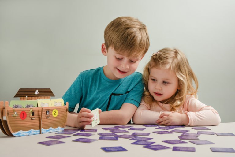 Two Children Playing Ark Buddies with Cards